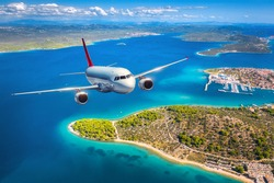 Airplane is flying over small islands and sea at sunset in summer. Aerial view of passenger airplane, tropical seashore, mountains with green trees, sky and blue water. Top view of aircraft. Travel
