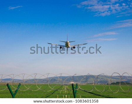airplane landing at the airport runway. barbed wire in the frame #1083601358