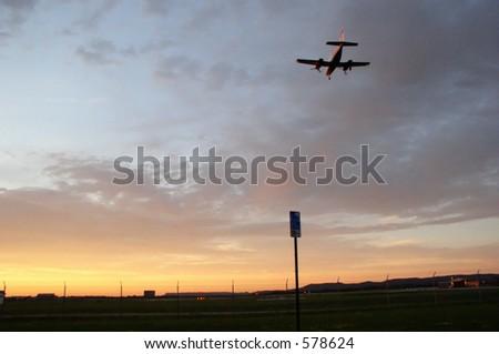 Airplane lands at sunset