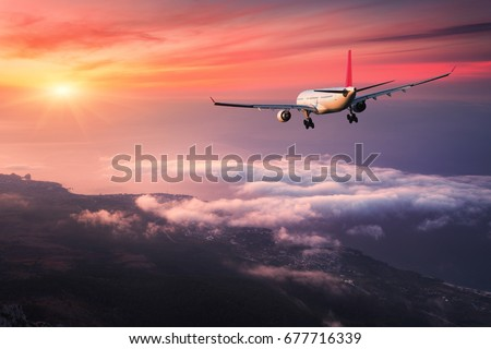 Airplane. Landscape with big white passenger airplane is flying in the red sky over the clouds at colorful sunset. Journey. Passenger aircraft is landing at dusk. Business trip. Commercial plane #677716339