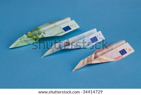 Airplane made from euro currency on blue background. - stock photo