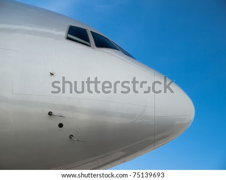 Airplane nose details against clear blue sky