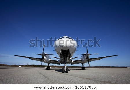 Airplane on the ground in front of blue sky