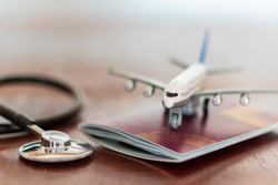 Airplane on top of a passport document and a Stethoscope. Healthcare and travel insurance concept