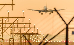 Airplane or aeroplane landing at the runway during sunset. Focus on the traffic lights Commercial aviation is a massive industry involving the transport of passengers daily on airliners.
