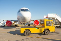 Airplane parked with a gangway, yellow ground service truck driving ahead