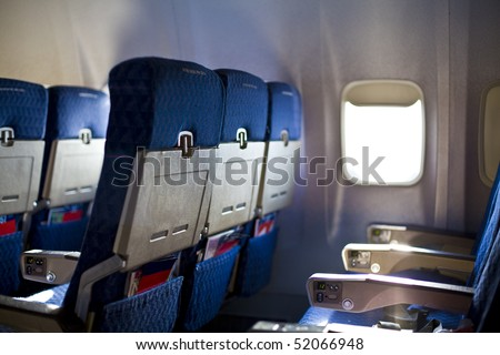 Airplane seat and window inside an aircraft focus on first seat in row