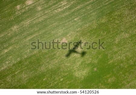 Airplane shadow on big green field