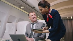 Airplane Stewardess Sending Digital tablet choose food order service on the plane flight, Business class. Flight Attendant Shows Tablet Computer with Menu to Caucasian Male Passenger. They're Inflight