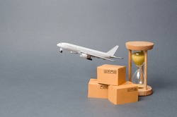 Airplane takes off behind the stack of cardboard boxes and a sand clock. concept of air cargo and parcels, airmail. Fast delivery of goods and products. Cargo aircraft. Logistics, connection