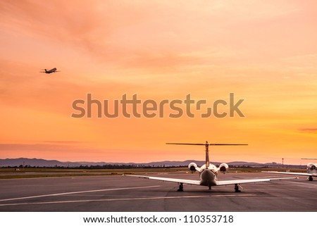 Airplane taking off at sunset. - stock photo