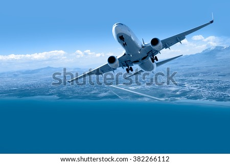 Airplane taking off from airport - Passenger airplane is flying over amazing mountains and sea  - Travel by air transport stock photo