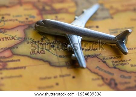 Airplane toy on Iraq part of world map. International flights to Iraq concept.