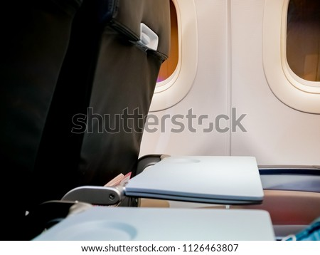 Airplane tray table on seat back at window seat , for put food meal on when eating or writing