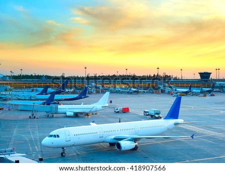 Airplane under loading in an airport at beautiful sunset