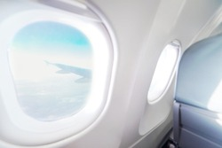 Airplane window view inside an aircraft. Window plane. Vacation destinations concept. Light blue seats and white interior with view on sky and wing of plane