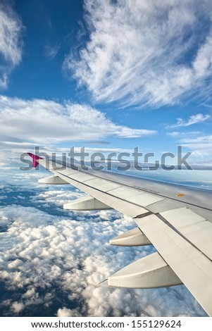 Airplane Wing against Blue Sky and Clouds