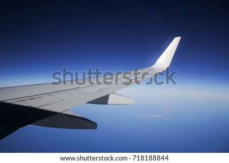 airplane wing during flying in blue sky #718188844