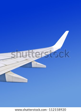 airplane wing during the flight on cloudless sky - stock photo