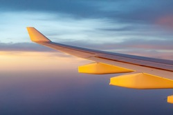 airplane wing flying in the sky, beautiful colours of evening sunset or morning sunrise lighting shining through clouds sky and on wing, commercial airline looking out window seeing wing side of plane