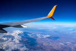 Airplane wing flying over white clouds and brown earth in a blue atmosphere. Aerial view of the planet from a plane window
