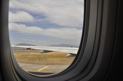 Airplane wing landing at the airport seen through the window. Andes mountain in the background.