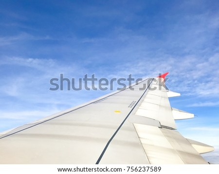 Airplane wing on blue skies and clouds background #756237589