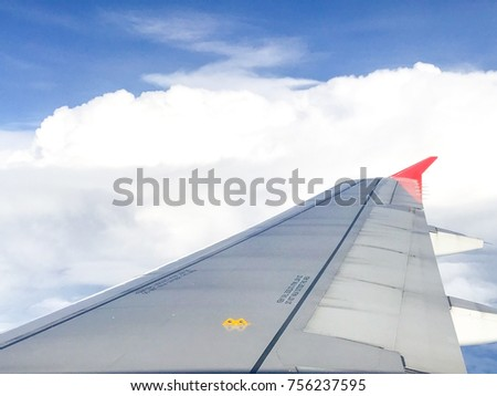 Airplane wing on blue skies and clouds background #756237595