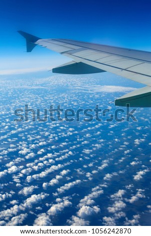 Airplane wing out of window, blue sky and clouds #1056242870