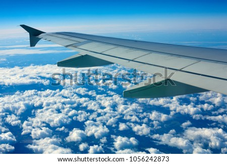 Airplane wing out of window, blue sky and clouds #1056242873