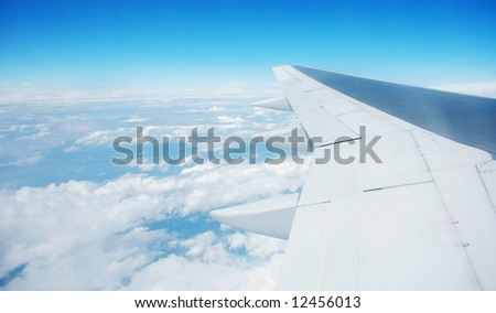 airplane wing over sea of clouds blue tones