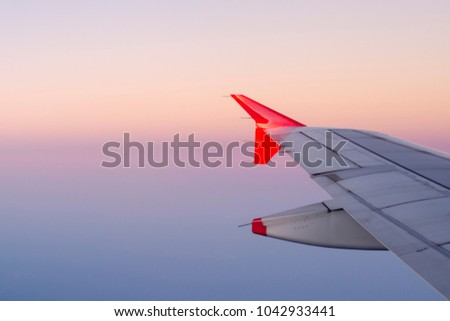 Airplane wing with a stunning colorful sunset sky in the background. Beauty of flying. Vacation vibes.  #1042933441