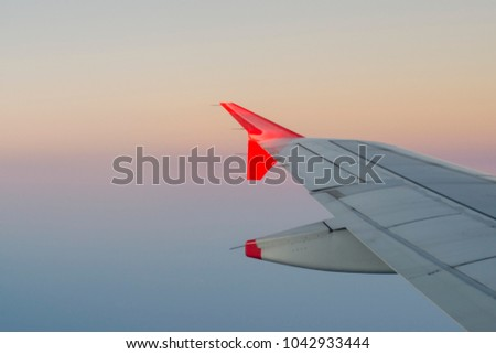 Airplane wing with a stunning colorful sunset sky in the background. Beauty of flying. Vacation vibes.  #1042933444