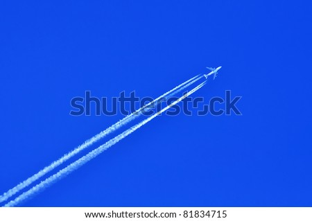 Airplane with four condensation trail on blue sky