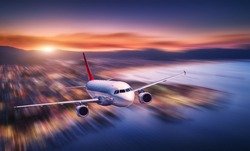 Airplane with motion blur effect is flying over sea coast at night. Landscape with passenger airplane, blurred buildings, city illumination, sea and sky. Aircraft. Business travel. Commercial plane