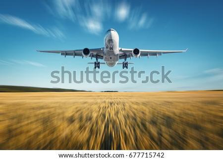 Airplane with motion blur effect. Landscape with white passenger airplane is flying, blue sky, wheat field at sunset in summer. Passenger airplane is landing. Commercial plane and blurred background
