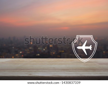 Airplane with shield flat icon on wooden table over blur of cityscape on warm light sundown, Business travel insurance and safety concept #1430837339