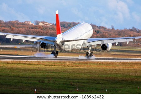 Airplane with two engines landing on runway back view - touchdown with tire smoke