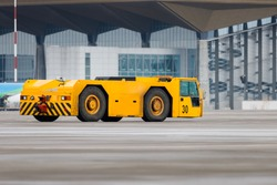 Airplane yellow pushback truck in moving at airport. Special, low profile vehicle - pushback tractors/tugs. Aircraft support maintenance vehicle at airport airside apron with terminal.