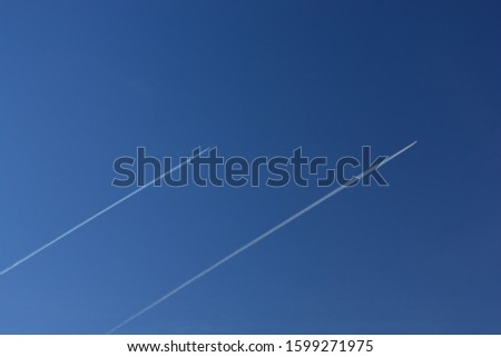 Airplanes leaves trace on clear blue sky. The trace called contrails, condensation trails or vapor trails, prouced by the aircraft engine exhaust, composed primarily of water, in form of ice crystals.