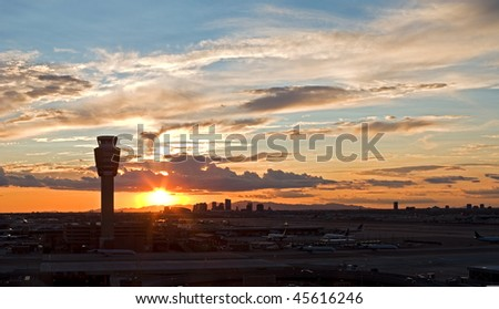 Airport at sunset with city skyline.