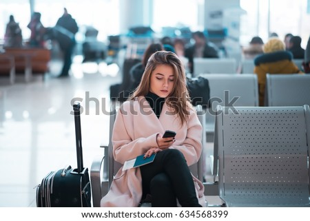 Airport business woman waiting in terminal. Air travel concept with casual businesswoman sitting with suitcase. Mixed race female professions.