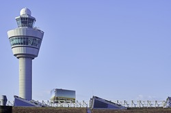 Airport control tower Amsterdam Schiphol in the early morning light against a blue sky.  Lots of copy space.