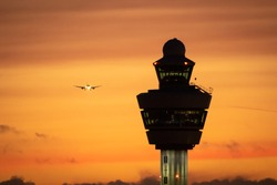 Airport control tower with a airplane landing in the background during sunset.