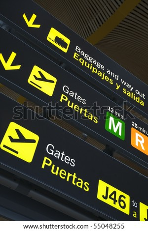 Airport departure gate sign written in English and Spanish in modern airport