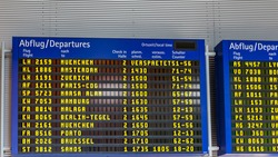 Airport flight information displayed on departure board, flight status changing. Flight schedule screen at airport showing different destinations.