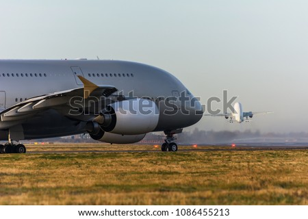 Airport live. While one airplane takes off, another one taxis to the airport runway. passenger jet planes delivers people and cargo. Taxiing for takeoff against the backdrop of another flying plane.