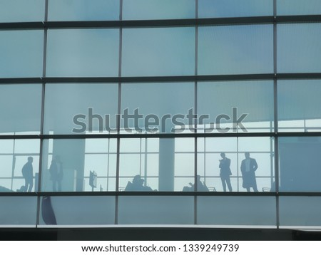 Airport passenger terminal waiting area. Groups of Passenger waiting time for boarding in the airplane. Seen from outside the terminal in silhouette.