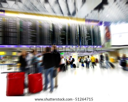 Airport passengers in a departure terminal with schedule display