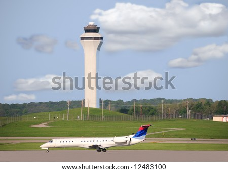 Airport Runway and Control Tower with planes on the runway and taxiway.
